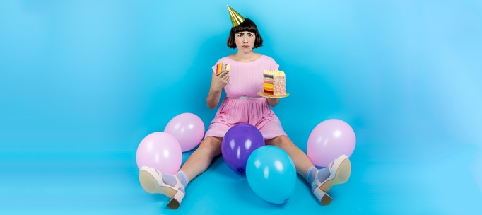 Image shows Brooke sitting on the floor in a pink party dress, holding a cake, surrounded by pastel balloons - Image Ali Wright