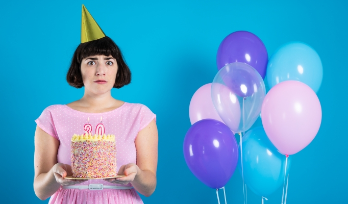 Image shows Brooke looking worried in a pink party dress, she is standing holding a birthday cake which has 30 lit candles in it. Pastel balloons float in the background - Image Ali Wright